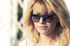 Woman with sunglasses. Horizontal portrait. Intense light. Blonde italian woman with sunglasses. Intense light and fair complexion royalty free stock images
