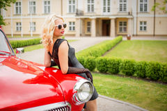 Woman with sunglasses  leaning against red retro car Stock Images