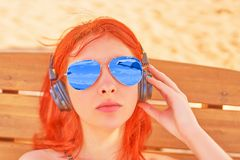 Woman in sunglasses listening to music on beach. stock photography