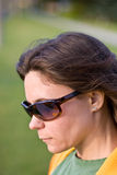 Woman with sunglasses and long hair looking down Royalty Free Stock Image
