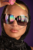 Woman in sunglasses looking through b Stock Image