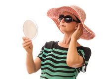 Woman in sunglasses looking in mirror Stock Images