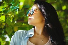 Woman in sunglasses looking at the sun. Portrait of beautiful girl with round glasses Stock Photo