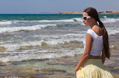 Woman in sunglasses is looking to the sea Royalty Free Stock Photo