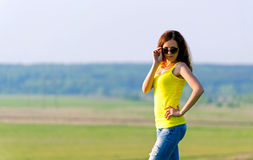 Woman in sunglasses looks at camera Royalty Free Stock Images