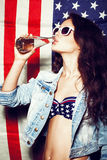 Woman in sunglasses with national usa flag. Beautiful young pretty woman in sunglasses with national usa flag in background drinking water. Lifestyle Royalty Free Stock Photography
