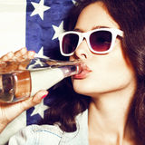 Woman in sunglasses with national usa flag. Beautiful young sexual woman in sunglasses with national usa flag in background drinking water. Lifestyle Royalty Free Stock Photos