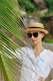Woman in sunglasses near palm tree Stock Photo