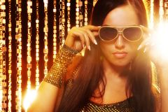Woman in sunglasses over golden curtains. Attractive woman in sunglasses over golden curtains stock images