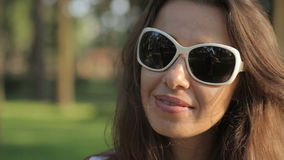 Woman in sunglasses in park. Looks at the camera stock video footage
