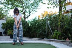 Woman playing minigolf, ready to hit the ball with a stick royalty free stock image