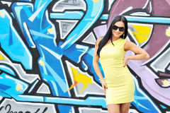 Woman in sunglasses posing against graffity wall. Beautiful young woman in sunglasses posing against graffity wall stock image