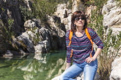 Woman with sunglasses resting next to a river in the mountains Royalty Free Stock Photography