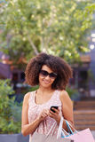 Woman in sunglasses sending a message on her phone Stock Photo