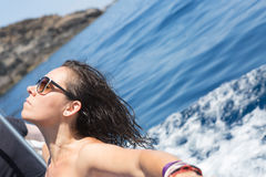 Woman in sunglasses on shipboard. Calm young woman with eyes closed taking sunbath while leaning on shipboard against of blue water. Copy space area Royalty Free Stock Images
