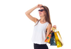 Woman in sunglasses with shopping bags. Young happy woman in white blouse and black skirt with sunglasses holding shopping bags on white background in studio Stock Images