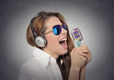 Woman with sunglasses singing with microphone. Headshot beautiful happy woman with sunglasses singing with microphone on grey wall background. Positive human royalty free stock photo