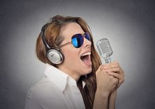 Woman with sunglasses singing with microphone Royalty Free Stock Image
