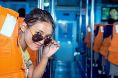 Woman with sunglasses sit on a ship Stock Images