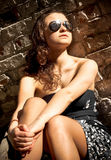 Woman in sunglasses sitting against brick wall Royalty Free Stock Images