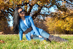Woman with sunglasses sitting in the autumn park Stock Images