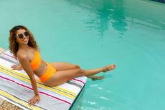 Woman in sunglasses sitting at the edge of swimming pool. High angle view of mixed-race woman in sunglasses sitting at the edge of swimming pool. Summer fun at royalty free stock photography