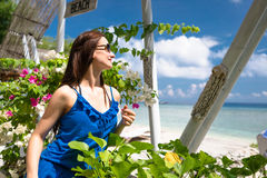 Woman with sunglasses sitting in garden near the sea Stock Images