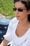 Woman in sunglasses sitting next to her suitcases Royalty Free Stock Images