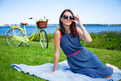 Woman in sunglasses sitting on the sea coast with vintage bicycle Stock Image