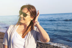 Woman with sunglasses smiling at the baach. Blue sea background Stock Images