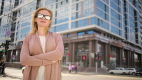 Woman in sunglasses standing on a busy street. woman, a resident of the city. stock video