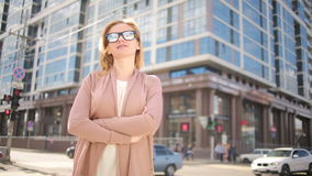 Woman in sunglasses standing on a busy street. woman, a resident of the city. stock video footage