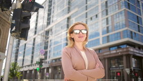 Woman in sunglasses standing on a busy street. woman, a resident of the city. stock footage