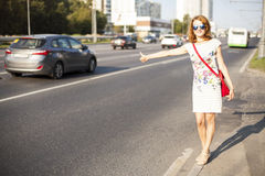 Woman with sunglasses standing in the street, calling  taxi Royalty Free Stock Images