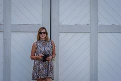 Stylish woman in sunglasses holding wallet and smartphone royalty free stock images