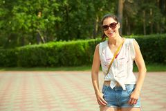 Woman in sunglasses in summer park. Portrait of a beautiful smiling woman in sunglasses in a summer park. elegance casual model outdoors Stock Photos