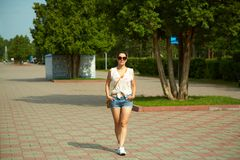 Woman in sunglasses in summer park. Portrait of a beautiful smiling woman in sunglasses in a summer park. elegance casual model outdoors Stock Photography