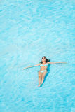 Woman with sunglasses swimming in the pool Stock Image
