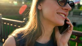 Woman in sunglasses talking on the smartphone while walking down the street at sunset, close up, close-up stock footage