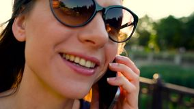 Woman in sunglasses talking on the smartphone while walking down the street at sunset, close up, close-up stock video