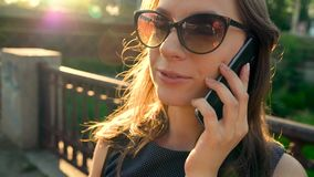 Woman in sunglasses talking on the smartphone while walking down the street at sunset, close up, close-up. Slow motion stock footage