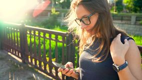 Woman in sunglasses using a smartphone outdoors at sunset stock footage