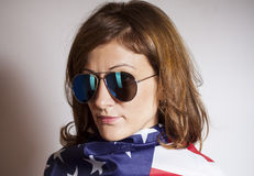 Woman with sunglasses wrapped in American flag. On gray Royalty Free Stock Photos