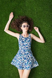 Woman with sunglasses. Young attractive woman relaxing on the grass and wearing sunglasses, summer and youth concept Stock Images