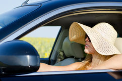 Woman in sunhat driving a car Stock Image