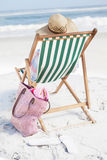 Woman in sunhat sitting on beach in deck chair Royalty Free Stock Photography