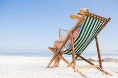 Woman in sunhat sitting on beach in deck chair using tablet pc Stock Photography