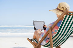 Woman in sunhat sitting on beach in deck chair using tablet pc. On a sunny day Stock Photos