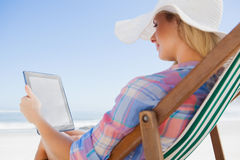 Woman in sunhat sitting on beach in deck chair using tablet pc Royalty Free Stock Photos