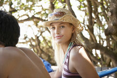 Woman In Sunhat Sitting Beside Friend Outdoors Royalty Free Stock Image